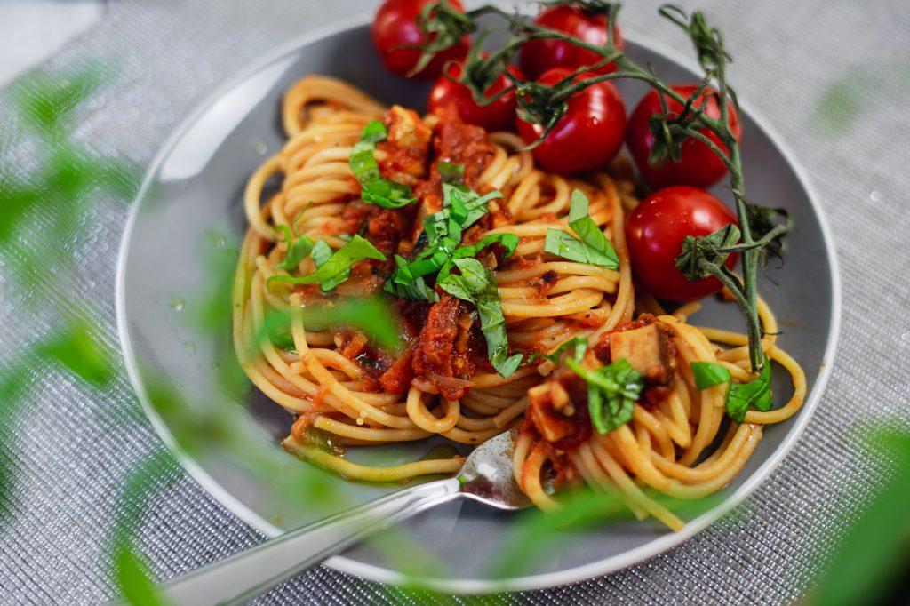 Spaghetti Napoli, schön garniert mit frischen Tomaten, Basilikum und Tofu-Bacon (Facon).